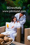 Photo of a happy smiling couple at a luxury resort spa. The man is massaging her shoulders as she smiles up at him. She has a glass of fresh squeezed orange juice in her hand.